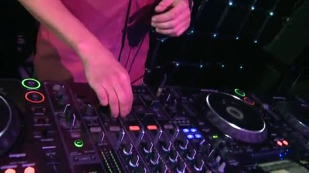 Closeup of hand of DJ on mixer and turntables. Scene. DJ equipment in night club. Concept of club music