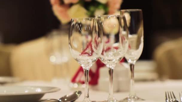 Detail sklenice na víno. Scénu. Prázdné víno brýle v elegantní restauraci na pozadí nádherné kytice