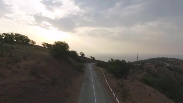 Letecký snímek auto na dálnici do pohoří. Střela. Přes horský průsmyk silnici směrem na krásné slunné oceánu