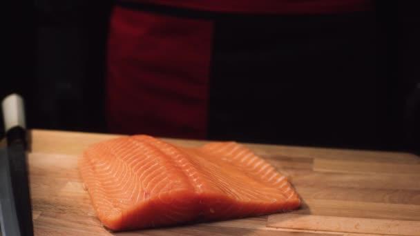 A fából készült deszka késsel nyers lazac filé részlete. Nézd a lédús darab, lazac, ízletes étel elkészítéséhez vágás előtt