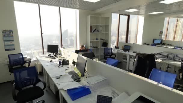 Vista dellufficio di affari con un solo dipendente seduto sul lavoro da solo. Vista della grande Openspace con gran lavoratore. Concetto del lavoro dufficio