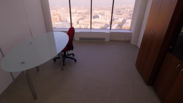 Pohled od panoramatické okno na městské krajiny. Malé útulné místnosti stůl, židli a skříň s panoramatickým oknem. Vnitřní prostory pro služební cesty zaměstnanců