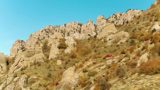 Magas hegység színes őszi zöld sárga rétek, sziklás hegycsúcs, felülnézet. Lövés. Kilátás a hegység sziklás terepen. A csodálatos hegyi táj ellen, tiszta kék ég