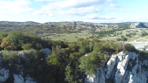 Top view of rocky landscape of valley. Shot. Panoramic landscape of mountain valley on sunny day. View of green mountainous terrain with areas of rocks