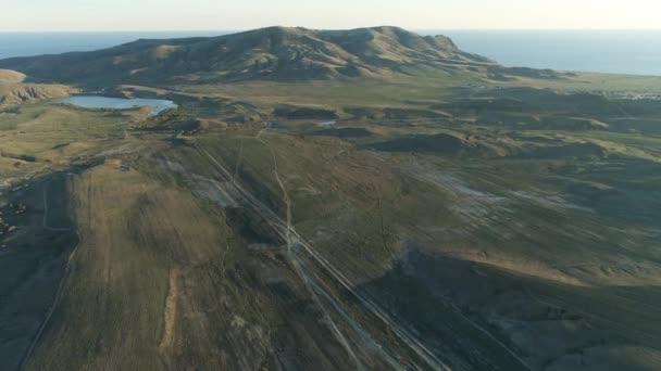 Panoramatický pohled shora na venkovské silnici. Střela. Malebná krajina pobřežní části kopcovité krajiny. Pohled shora zelené kopce proti modré obloze s západ slunce a moře na obzoru