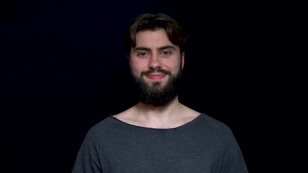Close up photo of a happy smiling bearded man, isolated on a black background. Handsome man wearing grey tshirt and smiling