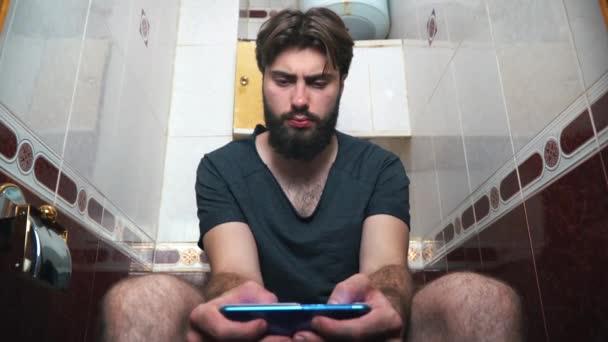 Mann benutzt Smartphone während er auf Toilette sitzt. er tippt eine Nachricht.
