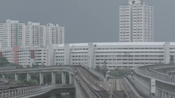 Modern subway train on a railroad in Sinapore on a city buildings background. Singapore mass rapid train MRT travels on the track.