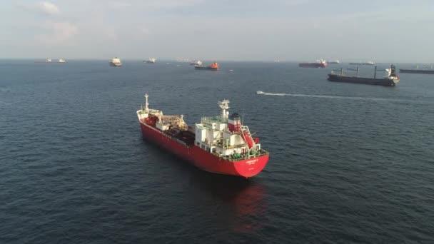 Antenna részére egy piros nagy barge lebegő a tengeren a part mentén. Lövés. A tengeri bárka az árufuvarozást végző más hajók, a háttér.