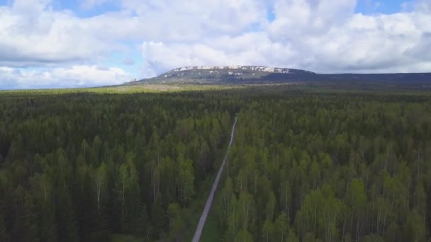Top view of horizon with rural road between forest and sky. Clip. Rocky mountain on horizon illuminated by sun against blue cloudy sky