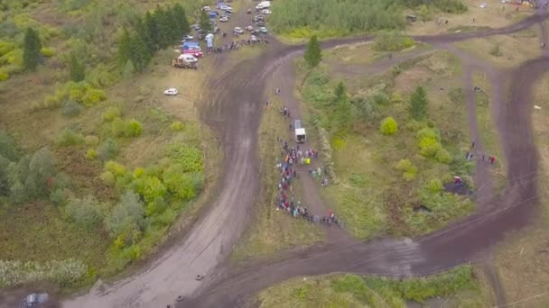 Top view of off-road racing with SUVs. Clip. View of finishing SUV racing in forest against crowds of fans
