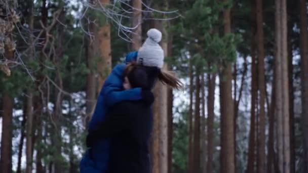Mladý pár, objímání a líbání v parku v zimě. Pár spolu šťastní. Mladý muž krouží svou přítelkyni bojující proti zimní les