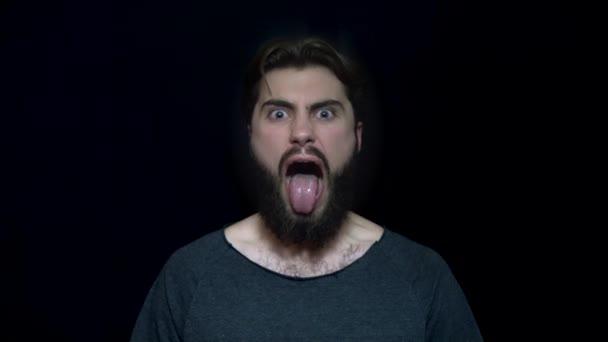 Mladý muž s plnovousem a jazykem trčí v rage. Angry young man šílenství s otevřenými ústy. Výrazy lidské tváře a emoce