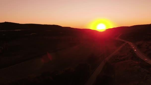 Červený západ slunce. Střela. Červené slunce nebe s jasný disk slunce částečně zakryté horami. Pohled shora provozu na venkovské silnici procházející venkovské oblasti na západ slunce