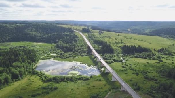 Pohled shora doprava na polní cestu v lese. Klip. Dálnice přes bažiny v lese s oblohou