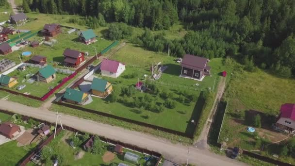 Top view of village in forest. Clip. Village life in forest terrain. Small houses with green teachers. Rest in village