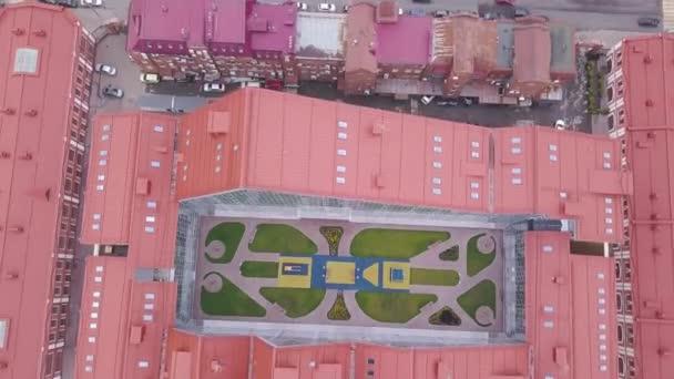Felülnézet épület nyílt tér közepén. Klip. Felülnézete U-alakú zárt komplex épület piros tetővel