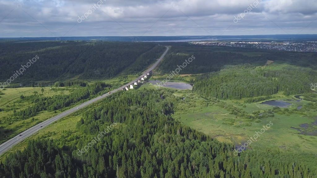Top view of bridge passing through in forest. Clip. Highway passes through swamp in forest to city on horizon. Traffic on rural highway in cloudy weather