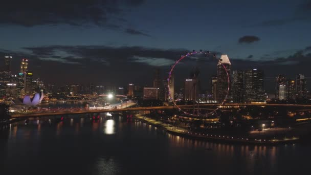 Singapore cityscape panorama by night with farris wheel behind the river. Aerial for Singapore night view with bright ferris wheel and the river