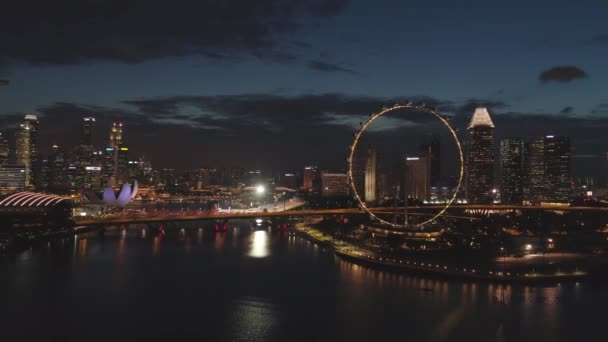 Singapore - 25 September 2018: Singapore cityscape panorama by night with farris wheel behind the river. Shot. Aerial for Singapore night view with bright ferris wheel and the river.