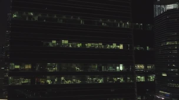 Singapur - 25 září 2018: čelní pohled na noc průčelí budovy se spoustou svítila okna. Střela. Fasáda vícepodlažní budova ze skla a oceli, úřadů a pracující lidé uvnitř