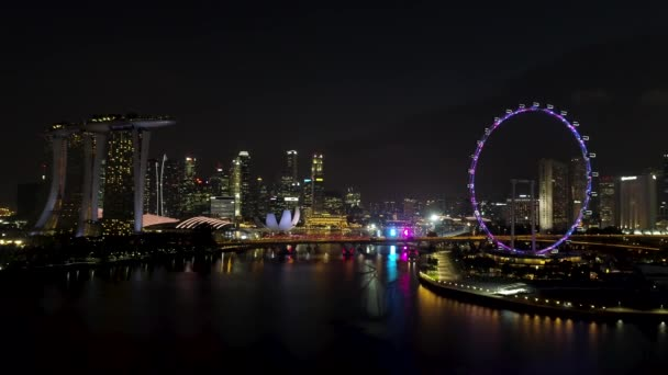 Singapore - 25 September 2018: Singapore city skyline at night with the river, purple lighted Ferris wheel and famous Marina Bay Sands Hotel. Shot. Breathtaking aerial view of night Singapore with
