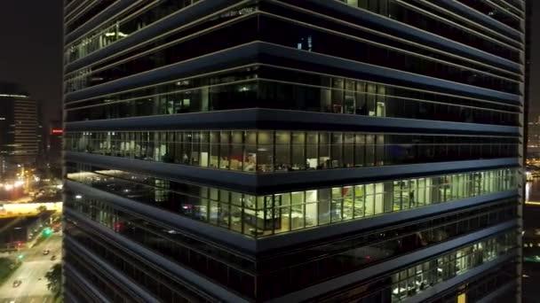 Singapur - 25 září 2018: zavřít do exteriéru moderní kancelářské budovy koutek s osvětlenými okny a lidé uvnitř. Střela. Letecké centrum kancelářská budova roh v noci, osvětlené