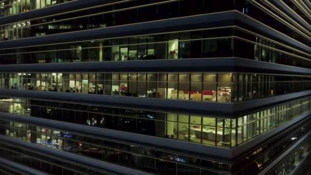 Detailní záběr pro exteriér moderní kancelářské budovy koutek s osvětlenými okny a lidé uvnitř. Letecké centrum kancelářská budova rohu v noci, osvětlené windows pozadí
