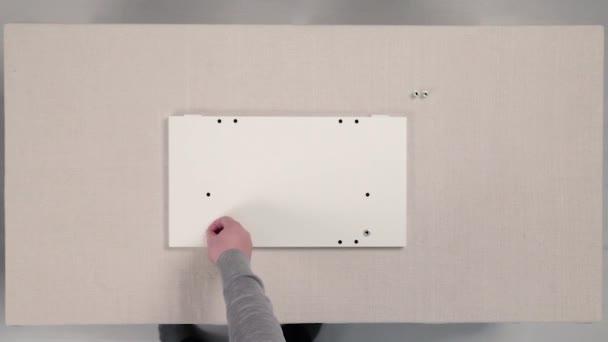 Nástroje pro montáž nábytku. V UK. Montáž nábytku, ruce v rukavicích zavřít až zašroubovat nábytku. Instalace a montáž nábytku, použití spojovacích prostředků, šroub pro šroubování do dřeva