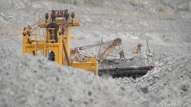 Bagger bewegt Erz in Eisenbahnwaggon im Steinbruch. Schweres Gerät.