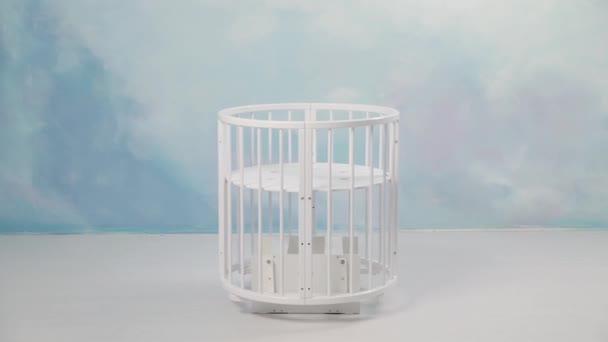 Baby bílá kolébku houpat v prázdné místnosti před zdí probarvené ve světle modré. V UK. Bílá malá postýlka kyvné z jedné strany na druhou v prázdné místnosti se světlem