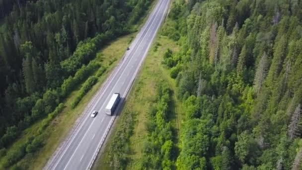 Pohled shora krajinu dálnice v lesnaté oblasti. Klip. Venkovské silnice s provozem osobních a nákladních automobilů bude město na obzoru. Cestování a doprava