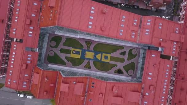 Szemközti nézet a nyílt tér közepén az épület. Klip. Nyílt helyen pihenni, zárt épületben találhatóak piros tetős tükrözött belső homlokzat közepén
