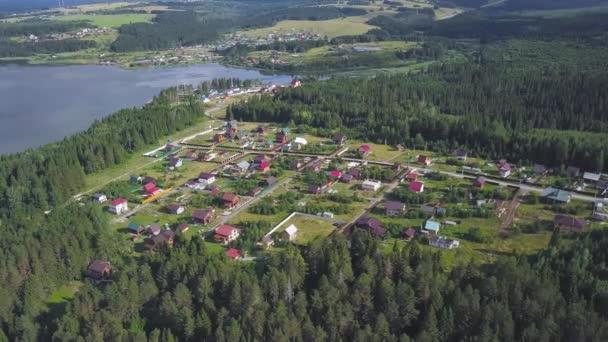 Pohled shora pobřežní města. Klip. Chalupa obec v lesnaté oblasti jako ráj míru a klidu. Panorama z vesnice se nachází na břehu široké řeky