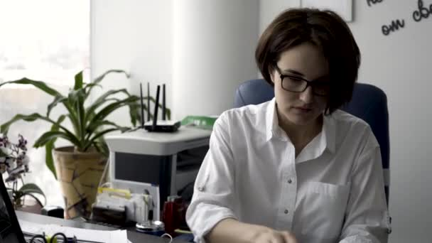 Attractive young office woman in white shirt working on the business papers, signing documents near green plant and printer. Female office worker arranging documents and putting her signature on them.