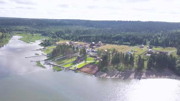 Top view of cottage village by lake. Clip. Country modern cottages with green lawn areas standing on shore of lake on background of dense forest. Rest in country in summer season