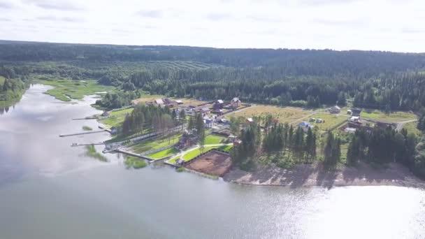 Felülnézet cottage falu-tó partján. Klip. Ország modern vendégházakat kínál zöld gyep területek állandó, háttérben a sűrű erdei tó partján. A nyári szezonban az ország többi