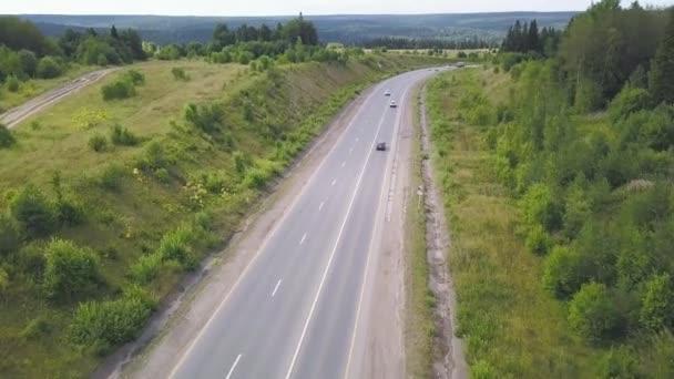 Pohled shora na venkovské silnici. Klip. Venkovské silnice s provozem v lese. Předměstské dálnice s osobních a nákladních automobilů. Cestování a doprava