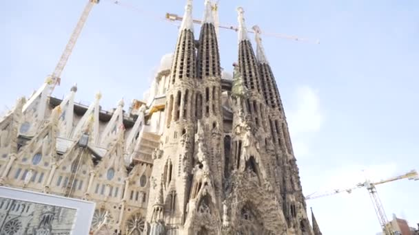 Spain - Barcelona, 12 August 2018: Man in leather jacket and black sun glasses taking photo of the gothic cathedral facade in a sunny day. Stock. Young tourist takes a picture of gothic style