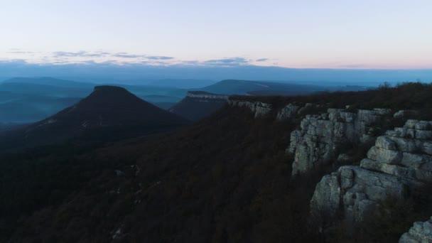 Ranní horská krajina s vlny mlhy. Střela. Pohled shora z hor v mlze a rock za soumraku. Mystic mlhavé krajina skal a hor s lesní porost v přítmí soumraku