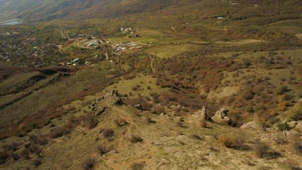 Letecká alpskou krajinu z malé vesničky v horách s modrou oblohu a podzimní žluté trávy. Střela. Pestré podzimní scenérie vesnice v údolí v Alpách