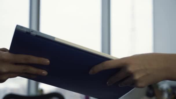 Detail pracovníka s modrou složku s papíry od tajemníka ruku v úřadu. Koncept papírování