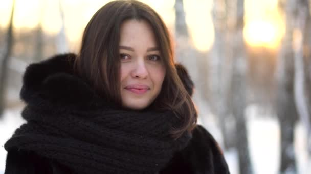 Close up portrait of beautiful brunette girl in black fur coat and big, knitted scarf outdoor in winter frost forest. Pretty, young woman smiling on blur sunset trees background.