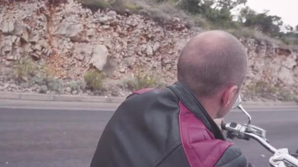 Közelkép hátsó nézet az ember a motorkerékpár. Stock. Idős szakmai motoros túrák motorkerékpár a vidéki temető. Férfi bőrkabát túrák motorkerékpár sisak nélkül