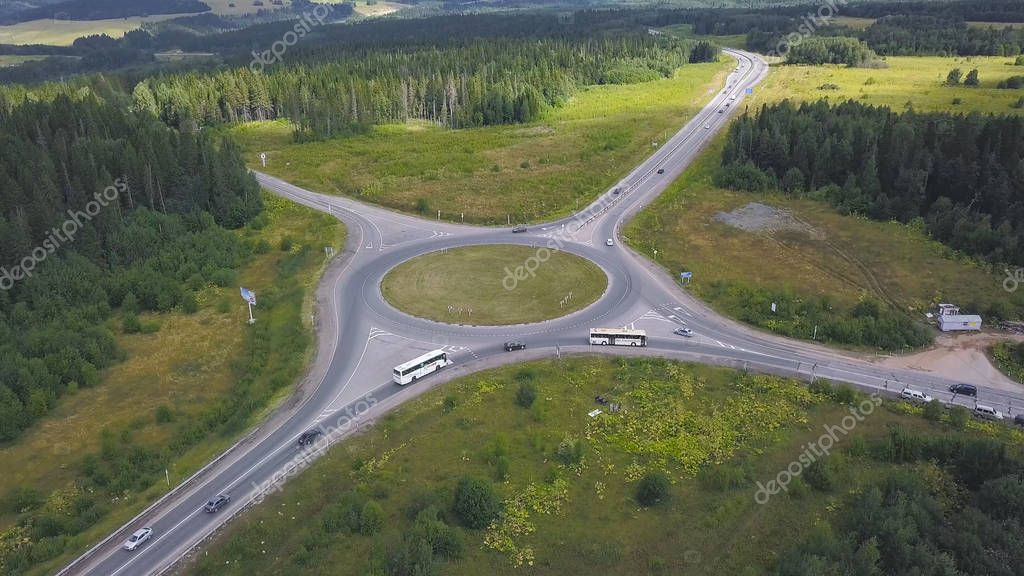 Top view of rural roundabout with traffic. Clip. Beautiful landscape of forest horizon and rural intersection of roads in ring. Rules of road at roundabout