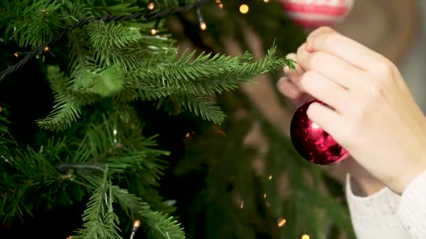 Close-up of womans hand hanging Christmas toy. Decorating Christmas tree. New year and Christmas holidays concept
