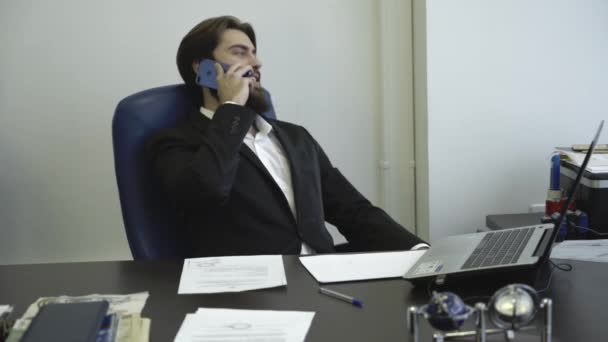 Confident and successful businessman talking on phone and sitting on a chair. Business negotiations.