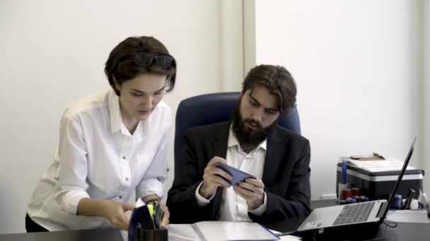 Woman secretary shows important documents to her bearded boss who is busy with playing smart phone games in the office, addiction to modern devices concept. Businessman signs papers angrily.