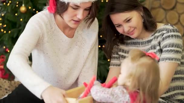 junges, schönes lesbisches Paar und ihr süßes kleines Mädchen neben Weihnachtsbaum mit roten Kerzen und Girlanden, Neujahrskonzept. gleichgeschlechtliches Paar mit Kind schaut sich Weihnachtsdekoration an.