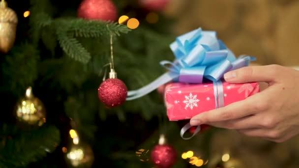 Detailní záběr pro ženské ruky držící vánoční dárek v červené barvě balicího papíru s velkými, modrou stužkou. Žena ruku s krásnou novoroční dárek na zelené, zdobené hračky Vánoční pozadí
